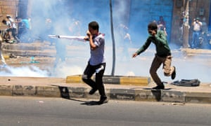 Yemenis run for cover as Houthis fire tear gas at a protest against their presence in Taiz, Yemen.