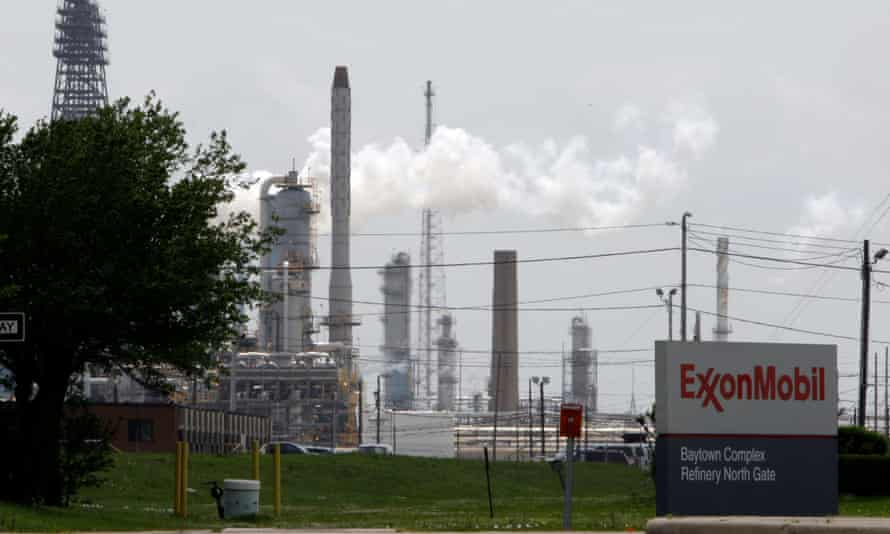 steam rises from towers at an Exxon Mobil refinery in Baytown, Texas