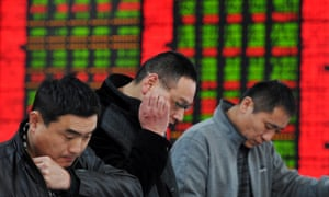 Investors look at share prices at a stock brokerage in Fuyang, east China.