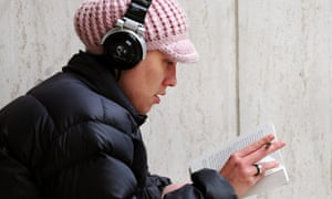 Woman reading a book while listening to headphones.