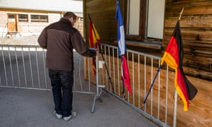 A man sets up a memorial with the flags of Germany, Spain and France in Vernet.
