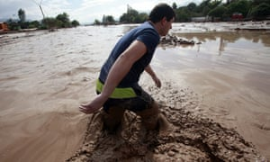 A man crosses a road amid the flooding in Copiapo.