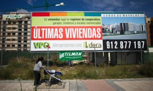 A pedestrian pushes a pram past a hoarding advertising new residential apartments in Madrid.