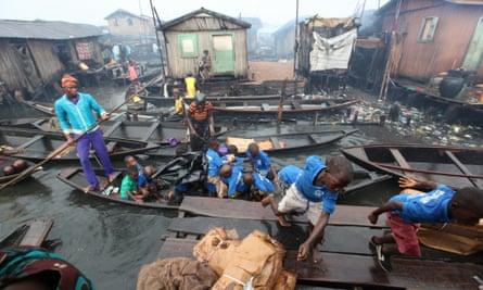 School children dash off a canoe in the rain in Makoko