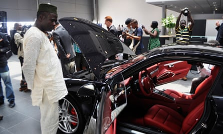 A man looks at a car at the Porsche dealership in Lagos.