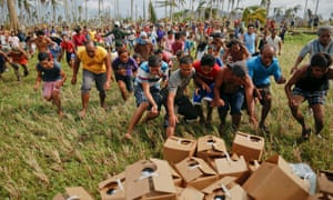 Typhoon Haiyan survivors rush to grab water dropped by plane.