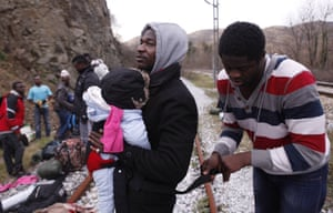 Jean-Paul Apetey of Ivory Coast receives help from Francis Tchiaze of Cameroon as he helps to carry Christian on their way to the town of Evzonoi, Greece.