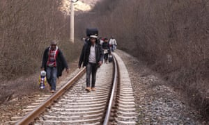 In this Saturday, Feb. 28, 2015 photo West African migrants walk on train tracks on their way towards the border with Macedonia near the town of Evzonoi, Greece.  The tide of hopeful migrants pours through the vulnerable 'back-door' countries in the hope of entering the 28-nation European Union, and although most people don't make it, the human tide continues to grow, according to Frontex, the EU agency that helps governments police the bloc s leaky frontiers.
