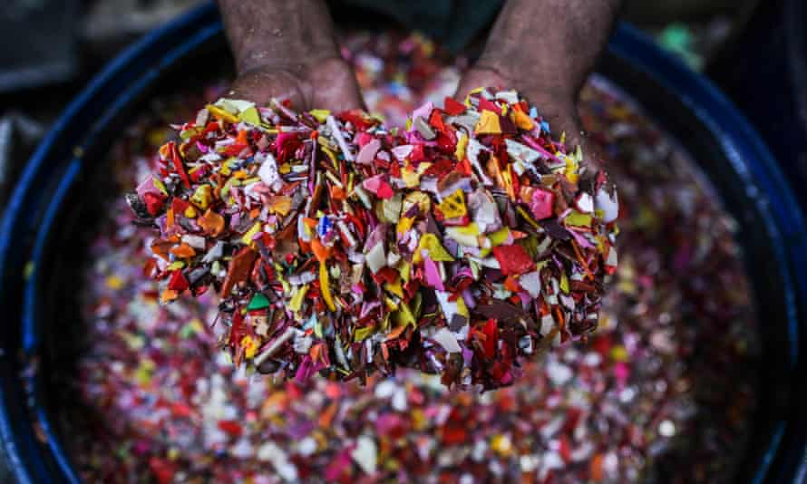 A worker washes shredded plastic waste for recycling in Mumbai, India.