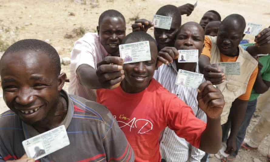 People displaced by Islamist militants display their voting cards in Yola, Nigeria.