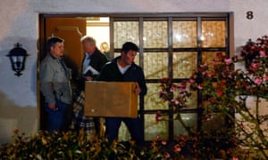 German police officers carrying items out of the home of Andreas Lubitz's parents