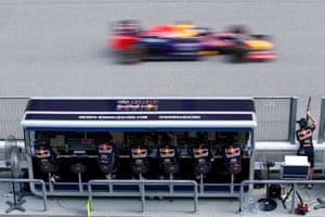 Daniel Ricciardo of Australia and Infiniti Red Bull Racing passes members of his team on the pit perch.