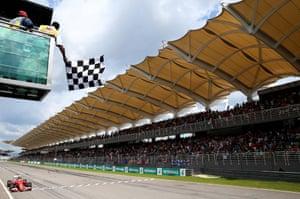 Sebastian Vettel of Ferrari crosses the finish line and takes the checkered flag.