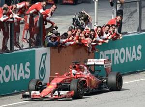 Ferrari team members celebrate as German driver Sebastian Vettel crosses the finish line.