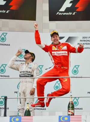 Ferrari driver Sebastian Vettel of Germany celebrates on the podium after winning the Malaysian Formula One Grand Prix with Lewis Hamilton in the background.