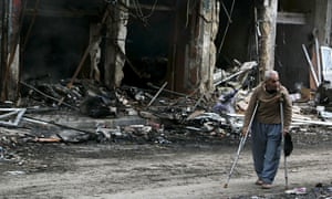 A man on crutches walks in a rebel-controlled area of Idlib, Syria, damaged by shelling.