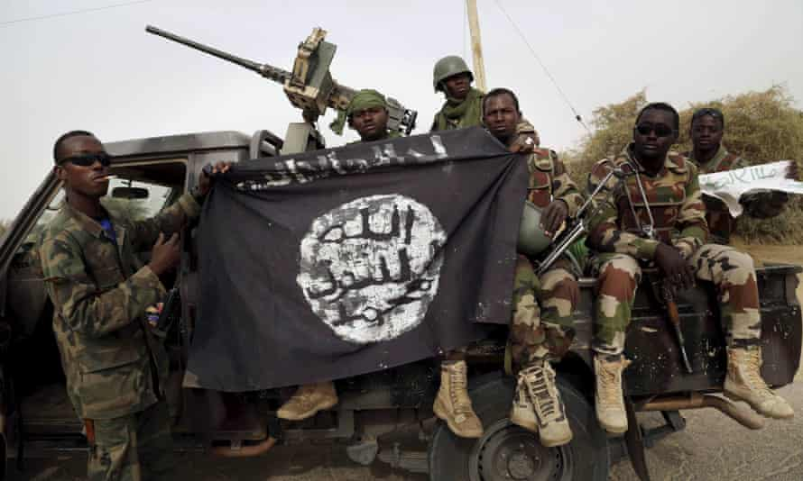 Nigerian soldiers hold up a Boko Haram flag seized in the retaken town of Damasak earlier this month.