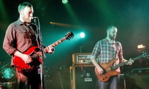 Barry Burns and Dominic Aitchison of Mogwai perform on stage in the UK, in 2014.