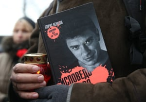 A man holds   Nemtsov's book Ispoved Buntaria (Confession of a Rebel)  as he queues to pay his respects.