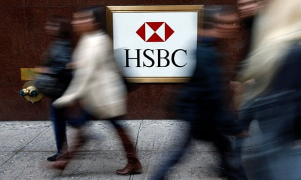 People walk past a branch of HSBC.