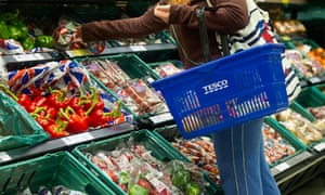 A customer browses the fruit and vegetable aisle in a Tesco Metro store.