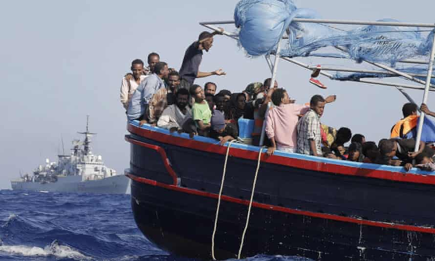 Some of more than 900  illegal migrants, are shipped to the mainland after being rescued by Italian Navy boat 'Fregata Euro'  (background) in the Mediterranean Sea, 12 September 2014.