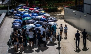 A section of the queue to pay tribute to Lee Kuan Yew alongside the Singapore River shelters under umbrellas from the searing afternoon sun.