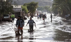 epa04680106 People walk along a street after a flood in Copiapo, Chile, 26 March 2015. The Chilean government declared a state of emergency on 25 March in Antofagasta, Tierra Amarilla, Alto del Carmen and Copiapo. The government said on 26 March that four people had died as a result of torrential rains and flooding over the past two days in the northern regions of Antofagasta and Atacama, while 22 others are listed as missing.  EPA/FELIPE TRUEBA