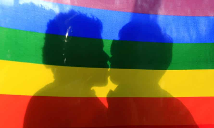 gay flag with two people kissing behind it