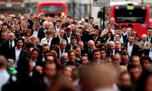 Commuters walk across London Bridge in the morning rush hour