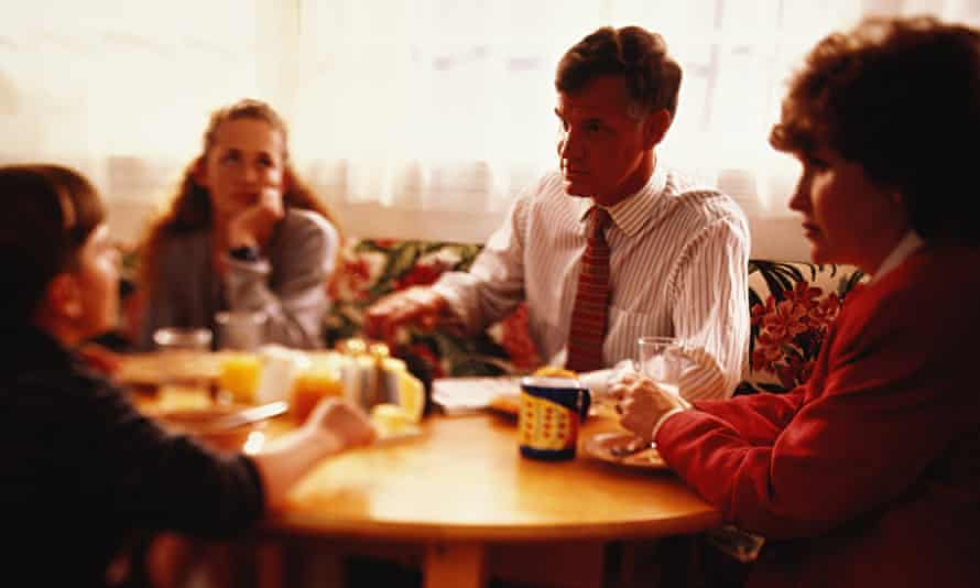 Bored teenager at breakfast with sister, mother and father in a tie