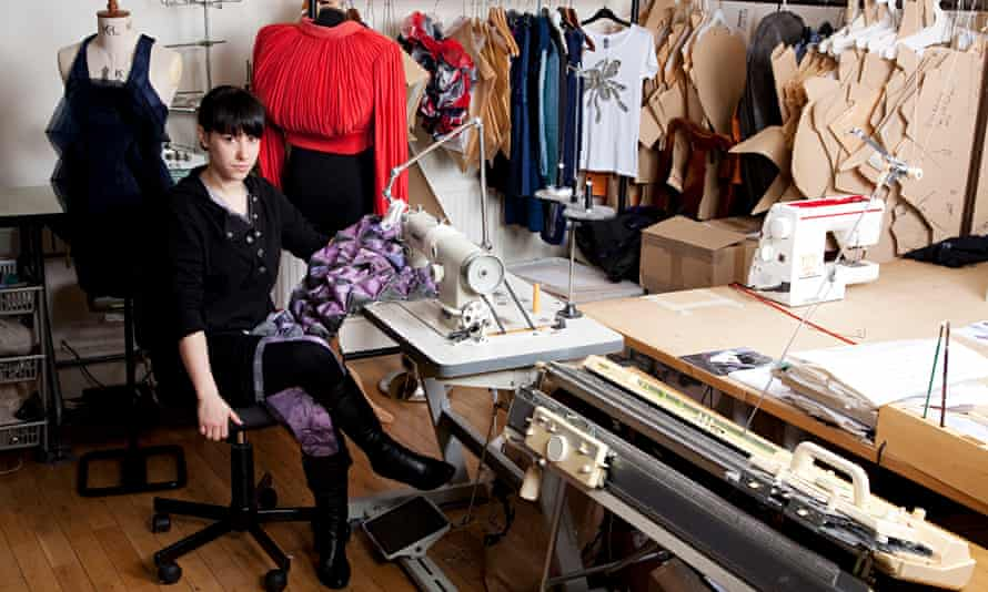 Eco fashion designer Ada Zanditon at a table with clothes behind her