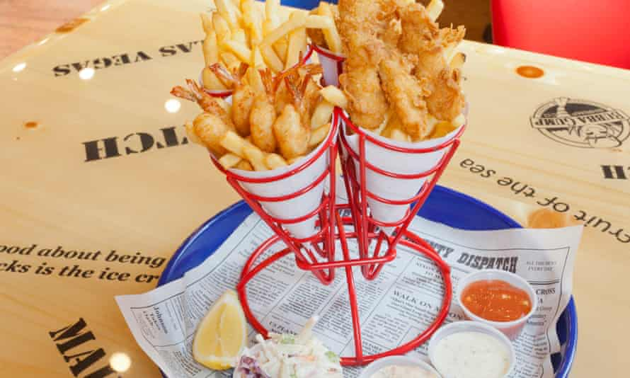 Metal holder containing paper cones of breaded shrimp, fried battered fish and 'hush pups' with sauces below in plastic cups