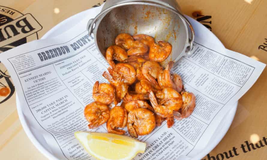 Shrimps spilling out of the horizontal metal-bucket Shrimper's Net Catch with a quarter of lemon