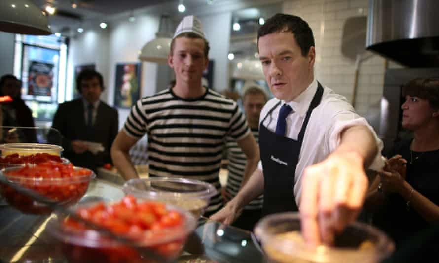 The chancellor, George Osborne, makes pizza with the help of a staff member during a visit to Pizza Express in Hove on Tuesday.