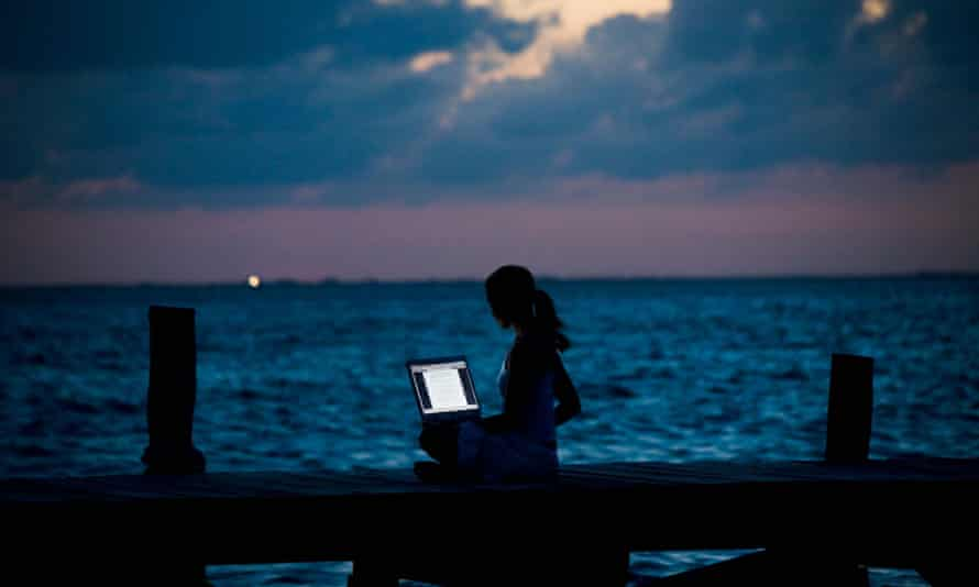 woman with laptop by sea