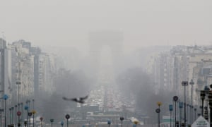 A faint view of the landmark Arc de Triomphe is seen through a foggy haze in Paris.