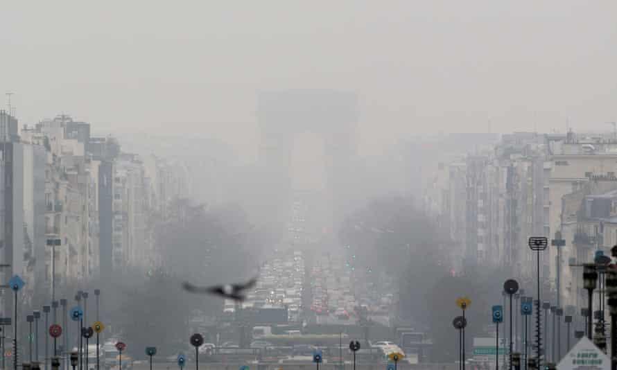 A faint view of the landmark Arc de Triomphe is seen through a foggy haze in Paris.