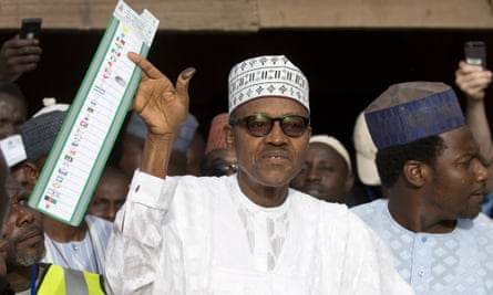 Muhammadu Buhari holds his ballot paper in the air before casting his vote in his home town of Daura, northern Nigeria, on Saturday.