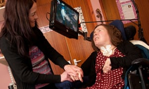 A woman suffering from locked-In syndrome after a brain tumour, cared for at home by her family