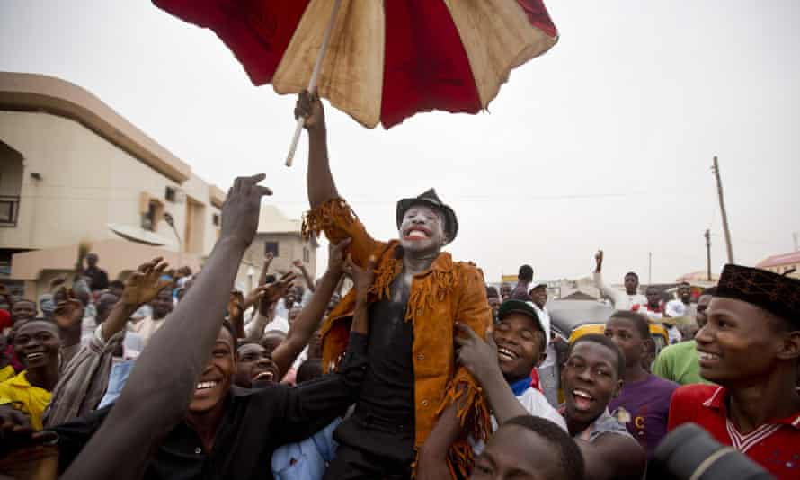 A supporter of president-elect Muhammadu Buhari, who is dressed up to represent and mock Goodluck Jonathan, celebrates in Kano.