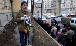 man stands  in Moscow on day of funeral with photo of Boris Nemtsov and red roses