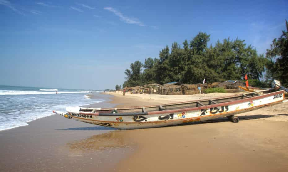 The beach at Abéné, Senegal, with fishermen's shacks, some selling fresh seafood.