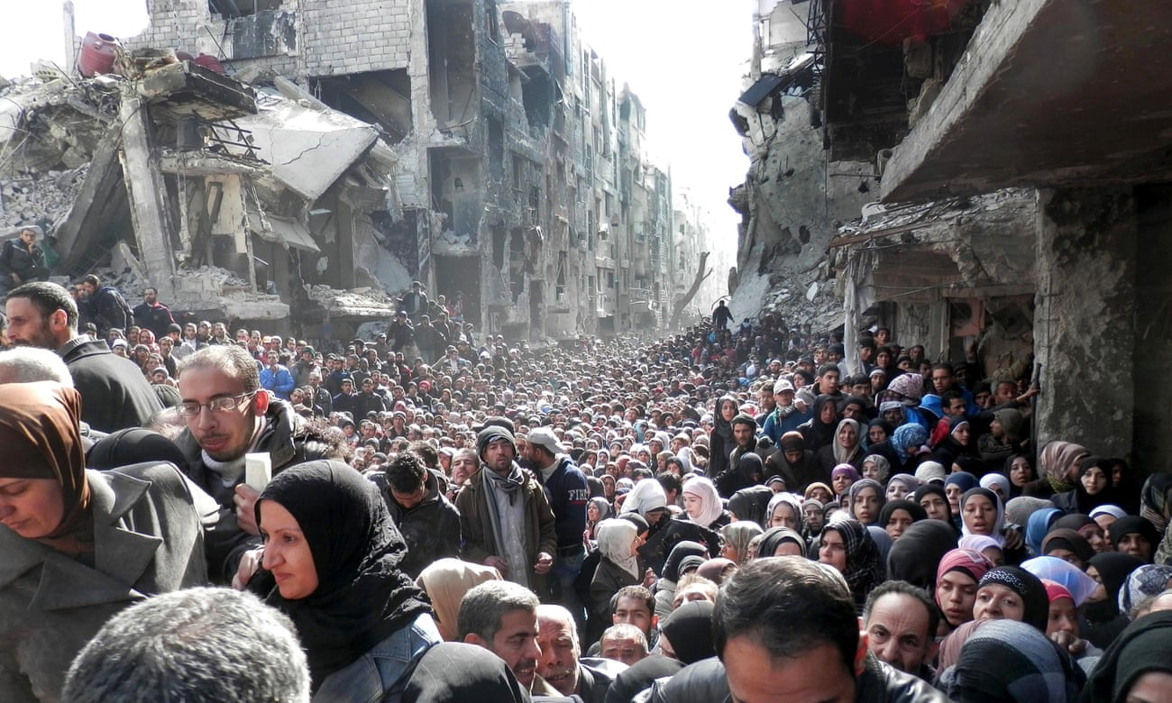 Palestinian refugees in Yarmouk, Damascus, queueing for food.