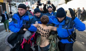 Swiss police officers drag away a Femen activist away from a demonstration at the World Economic Forum (WEF) in Davos in January 2015.