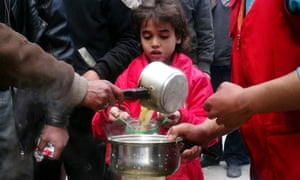 A girl receives soup from Kafaf, a charitable foundation, in Yarmouk