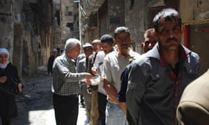 Palestine refugees in Yarmouk queue for food distributed by UNRWA.