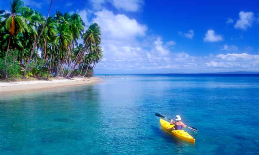 A woman sea kayaking near a tropical beach in Fiji.  Ocean cycles may have lulled us into a false sense of security by temporarily slowing global surface warming.