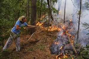A volunteer clears old brushwood on a wine farm in Kirstenbosch on the outskirts of Cape Town. Firefighters said the wildfire raging around Table Mountain is still not under control after four days fighting the blaze