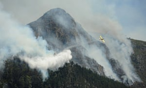 Helicopters and planes assist firefighters in battling the blaze near the Tokai Forest